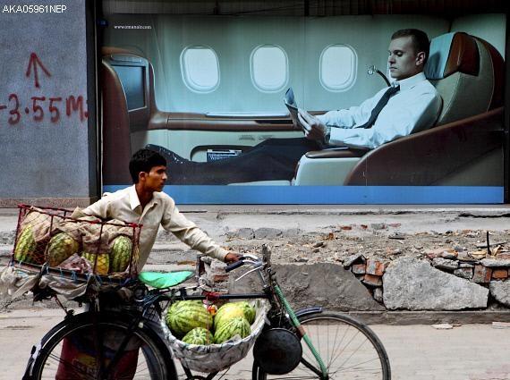 航空会社ファーストクラスの広告看板の前を通りゆく行商人